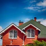 美丽的房子的绿色屋顶有好的窗口和蓝色的 免版税库存照片