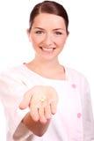 美丽的护士提供的药片微笑 图库摄影