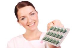 美丽的护士提供的药片 库存图片