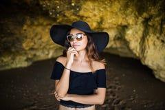 美丽的拉丁晒日光浴在岩石的妇女认为与帽子的和太阳镜在夏天职业时间靠岸 免版税库存照片