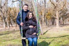 美丽的拥抱在摇摆的孕妇和她英俊的丈夫肚子 库存图片