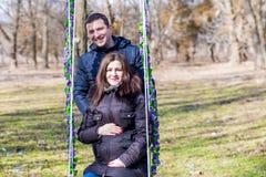 美丽的拥抱在摇摆的孕妇和她英俊的丈夫肚子 图库摄影