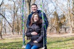 美丽的拥抱在摇摆的孕妇和她英俊的丈夫肚子 免版税库存照片