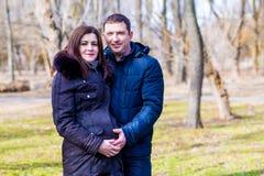 美丽的拥抱肚子的孕妇和她英俊的丈夫 免版税库存图片