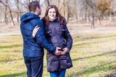 美丽的拥抱肚子的孕妇和她英俊的丈夫 库存图片