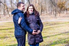 美丽的拥抱肚子的孕妇和她英俊的丈夫 免版税库存照片
