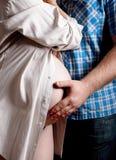 美丽的拥抱肚子的孕妇和她英俊的丈夫 图库摄影