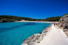 美丽的拥挤海滩用在夏季的绿松石水, Cala Modrago,马略卡 免版税库存照片