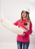 美丽的拿着图纸的妇女土木工程师 免版税库存图片