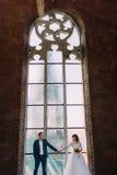 美丽的握在老哥特式窗口前面的新娘佩带的白色礼服和时髦的新郎手  免版税库存照片
