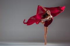 美丽的摆在灰色演播室背景的妇女舞蹈家佩带的褐红的泳装 库存图片