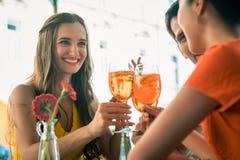 美丽的敬酒与一份刷新的饮料的妇女和她的最好的朋友 库存图片