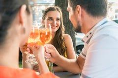 美丽的敬酒与一份刷新的饮料的妇女和她的最好的朋友 库存照片