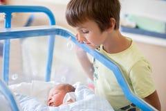 美丽的新出生的男婴,放置在小儿床在产前医院, 免版税库存图片