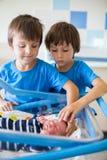 美丽的新出生的男婴,放置在小儿床在产前医院, 免版税图库摄影