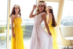 美丽的新娘和两个女傧相一起黄色相似的礼服的在海餐馆 免版税库存图片