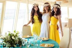美丽的新娘和两个女傧相一起黄色相似的礼服的在海餐馆 库存图片