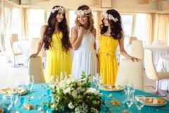 美丽的新娘和两个女傧相一起黄色相似的礼服的在海餐馆 免版税库存照片