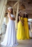 美丽的新娘和两个女傧相一起黄色相似的礼服的在海餐馆 库存照片