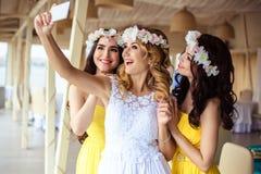 美丽的新娘和两个女傧相一起黄色相似的礼服的在海餐馆 图库摄影
