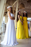 美丽的新娘和两个女傧相一起黄色相似的礼服的在海餐馆 免版税图库摄影