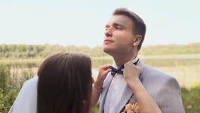 美丽的新娘和新郎一起是在自然在湖旁边 他们在眼睛互相看与 股票录像