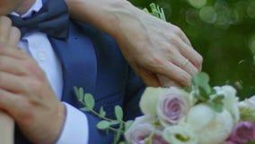 美丽的新娘和新郎在一个晴朗的公园,关闭亲吻  股票录像
