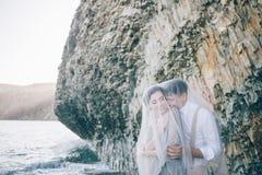 美丽的新娘和新郎在一面纱以下在海附近,谈话和微笑 库存照片