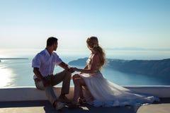 美丽的新娘和新郎在他们的在希腊海岛圣托里尼上的夏天婚礼之日 库存图片