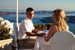 美丽的新娘和新郎在他们的在希腊海岛圣托里尼上的夏天婚礼之日 图库摄影