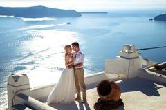 美丽的新娘和新郎在他们的在希腊海岛圣托里尼上的夏天婚礼之日 免版税库存图片