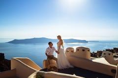 美丽的新娘和新郎在他们的在希腊海岛圣托里尼上的夏天婚礼之日 免版税库存照片