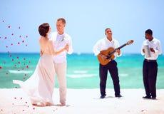 美丽的新娘和新郎跳舞在热带海滩,实况音乐 免版税图库摄影