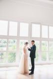 美丽的新娘和新郎画象与面纱在面孔 拥抱时髦的爱恋的婚礼的夫妇亲吻和 免版税库存照片