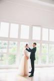 美丽的新娘和新郎画象与面纱在面孔 拥抱时髦的爱恋的婚礼的夫妇亲吻和 免版税库存图片