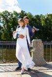 美丽的新娘和滑稽的新郎渠道堤防的在夏天 图库摄影