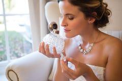 美丽的新娘嗅到的香水,当坐扶手椅子时 免版税库存照片