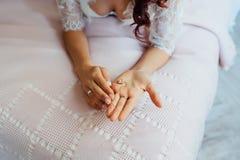 美丽的新娘在她的手上的拿着一条项链 库存照片