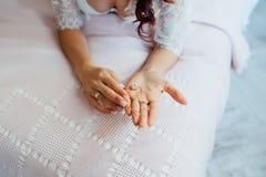 美丽的新娘在她的手上的拿着一条项链 免版税图库摄影