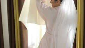 美丽的新娘在婚礼前接触婚礼礼服 股票录像