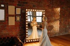 美丽的新娘在镜子附近站立并且调查她的反射 免版税库存图片