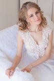 美丽的新娘坐在女用贴身内衣裤的一个白色长沙发 库存照片