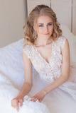 美丽的新娘坐在女用贴身内衣裤的一个白色长沙发 免版税库存图片