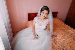 美丽的新娘坐床在等待和举行逗人喜爱的小的婚礼钮扣眼上插的花的窗口附近 免版税库存图片