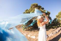 美丽的新娘年轻人 举长的新娘面纱的风 库存图片