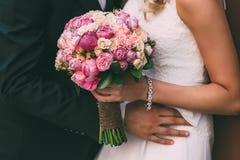美丽的新娘拿着与桃红色玫瑰和牡丹的婚礼花束 新郎由腰部的容忍妇女 免版税库存照片
