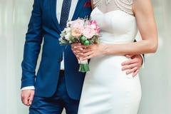 美丽的新娘拿着与桃红色玫瑰和牡丹的婚礼花束 新郎由腰部的容忍妇女 库存照片