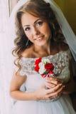 美丽的新娘特写镜头画象拿着与红色和白玫瑰的婚礼礼服的逗人喜爱的花束 库存照片