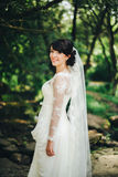 美丽的新娘白色礼服在森林里 库存照片