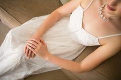 美丽的新娘的中央部位婚礼礼服的在家坐沙发 免版税库存图片